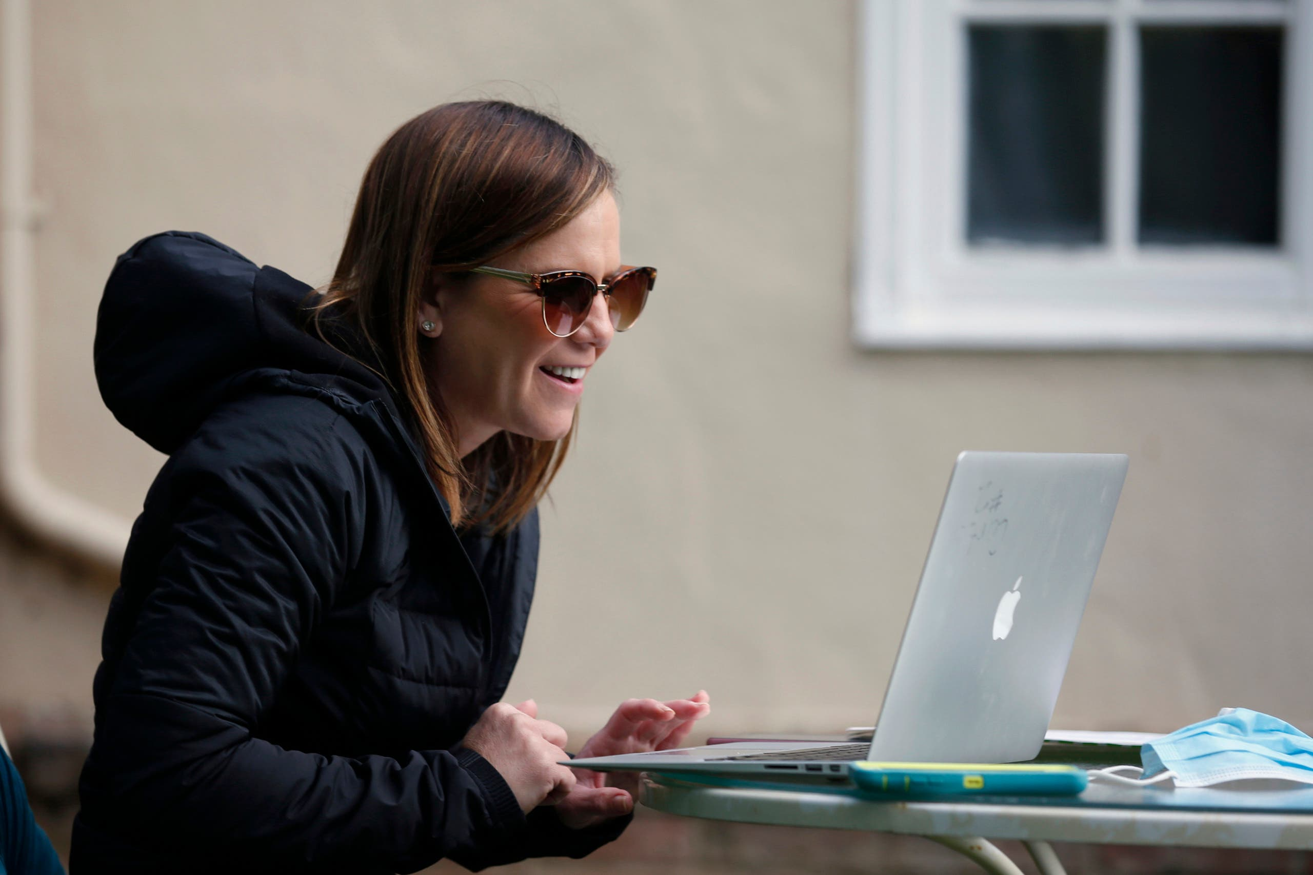 Kelly Dighero, a 3rd grade teacher at Phoebe Hearst Elementary School, holds her first online meeting with students and parents on the front lawn of her home in Sacramento, Calif. on April 13, 2020. (AP)