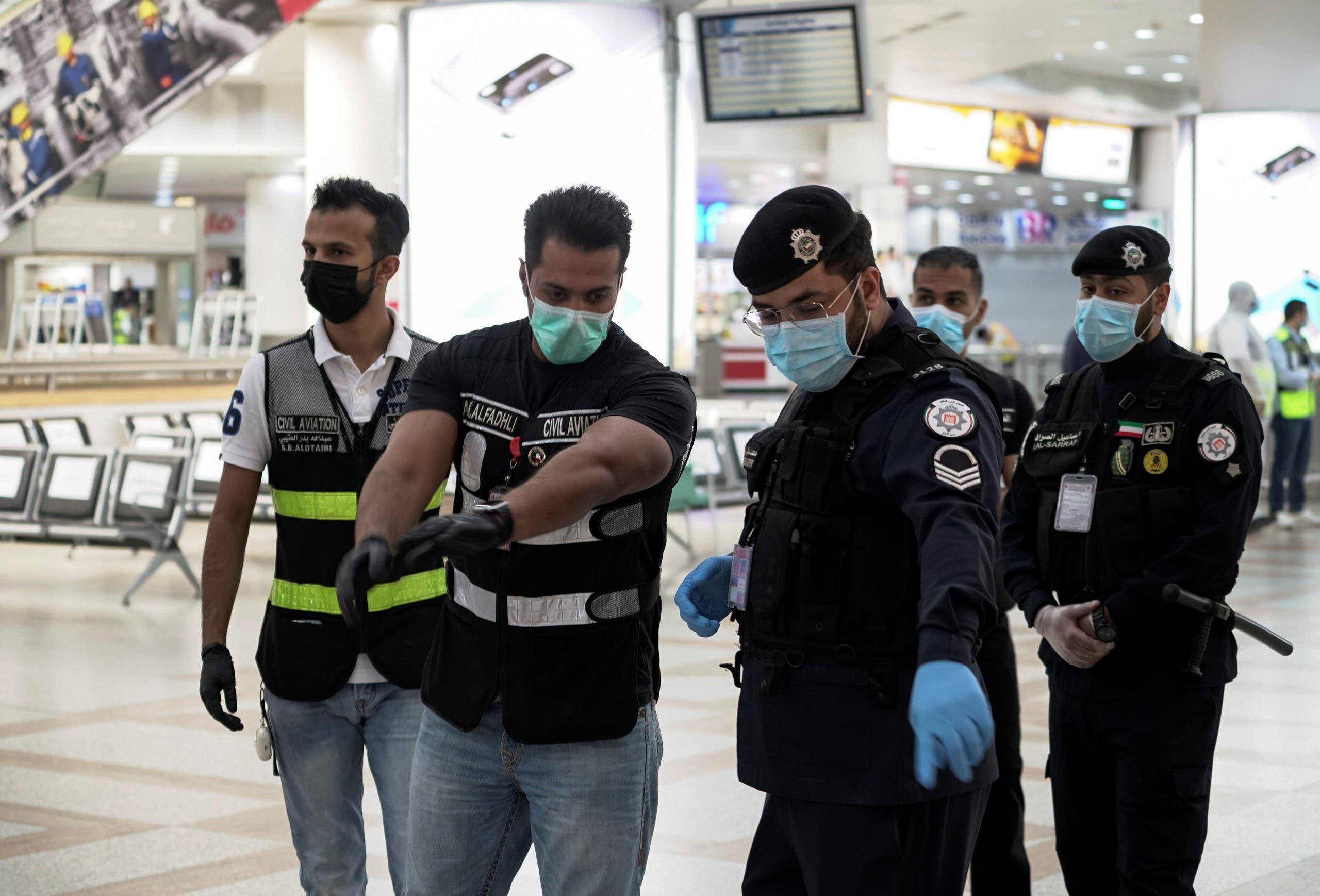 شرطيون وعاملون في مطار الكويت يستعدون لوصول طائرة ركاب تقل كويتيين تم إجلاؤهم من الخارج