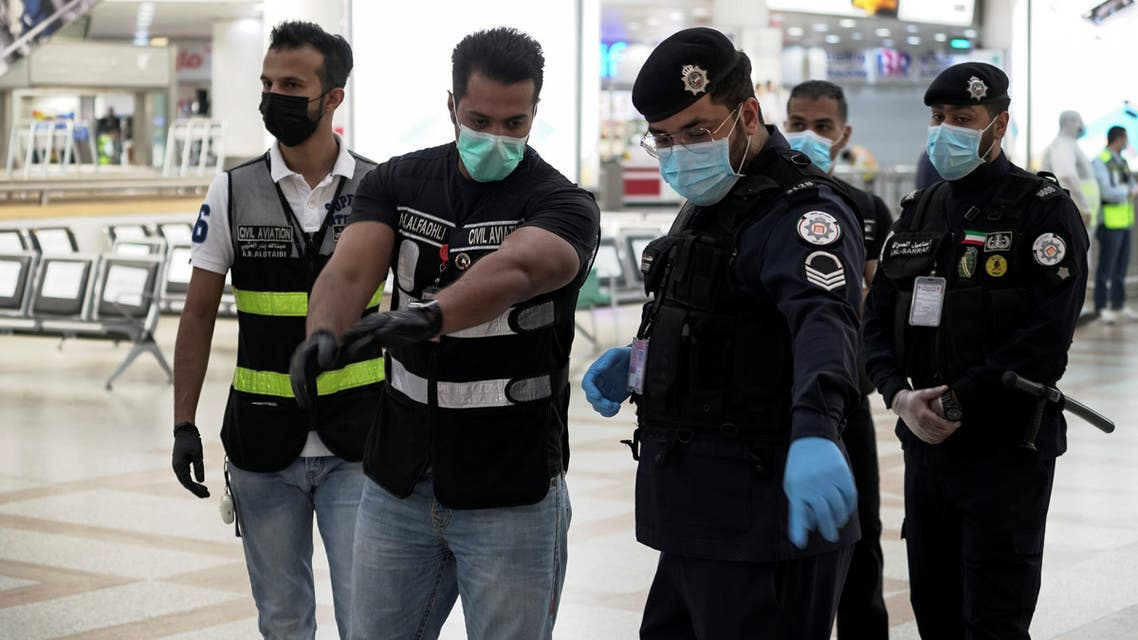 Police and civil aviation personnel wearing protective face masks work at the Kuwait Airport as the repatriation process of Kuwait citizens continues, following the outbreak of the coronavirus disease (COVID-19), in Kuwait City, Kuwait April 21, 2020. REUTERS/Stephanie McGehee
