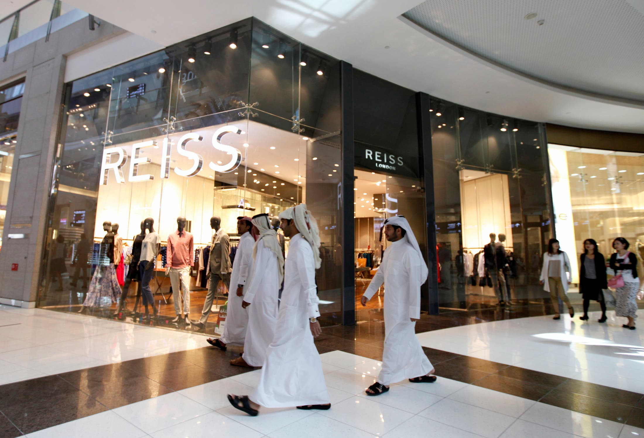 Men walk past a Reiss store at Dubai Mall shopping center in Dubai, February 5, 2012. (Reuters)