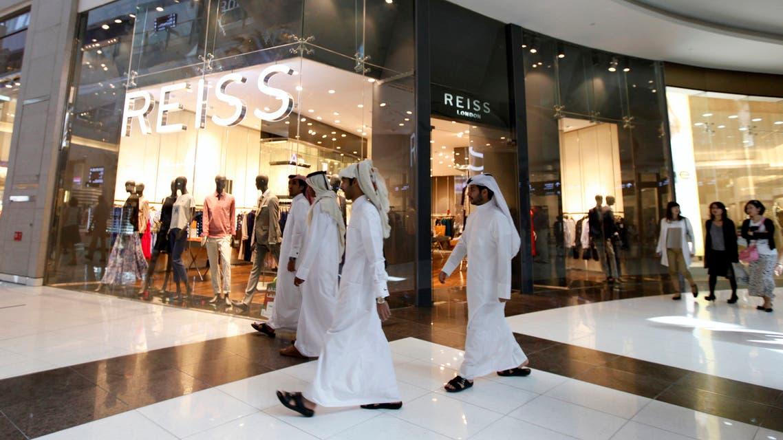 Men walk past a Reiss store at Dubai Mall shopping center in Dubai, February 5, 2012. (Reuters)