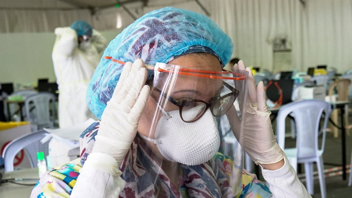 A Kuwaiti doctor adjusts her protective face shield ahead of the arrival of a planeload of repatriated Kuwaiti citizens at a makeshift field testing center, following the outbreak of the coronavirus disease (COVID-19), at Kuwait Airport, in Kuwait City, Kuwait April 21, 2020. REUTERS/Stephanie McGehee