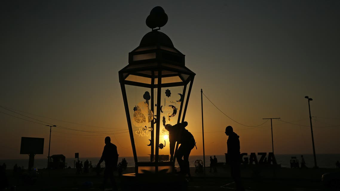 A man installs a giant traditional fanous lantern, a decoration used to celebrate the start of the Muslim holy month of Ramadan, at al-Shati camp for Palestinian refugees in the central Gaza Strip on April 23, 2020. (AFP)