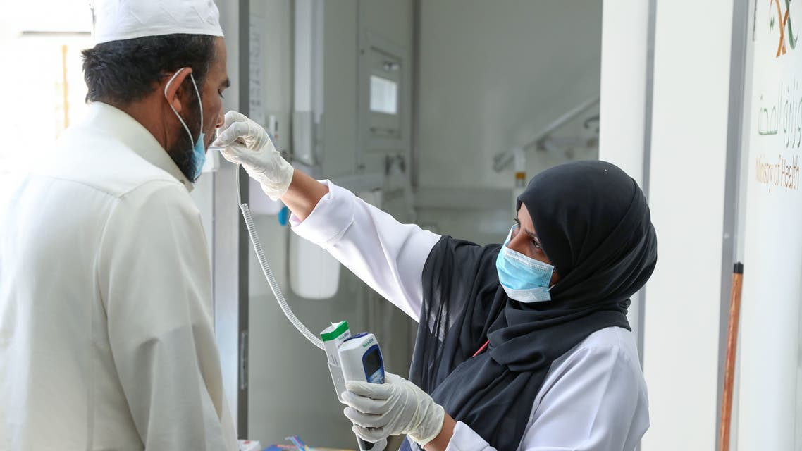 A Saudi nurse checks a patient's temperature at a mobile clinic catering for the residents of Ajyad Almasafi district in the holy city of Mecca, on April 7, 2020, which authorities have sealed-off, along with other major cities, amid measures to curb the spread of COVID-19. Saudi Arabia's health minister warned of a huge spike in coronavirus cases of up to 200,000 within weeks, state media reported, a day after the kingdom extended the duration of daily curfews in multiple cities, including the capital, to 24 hours in a bid to limit the spread of the deadly virus.