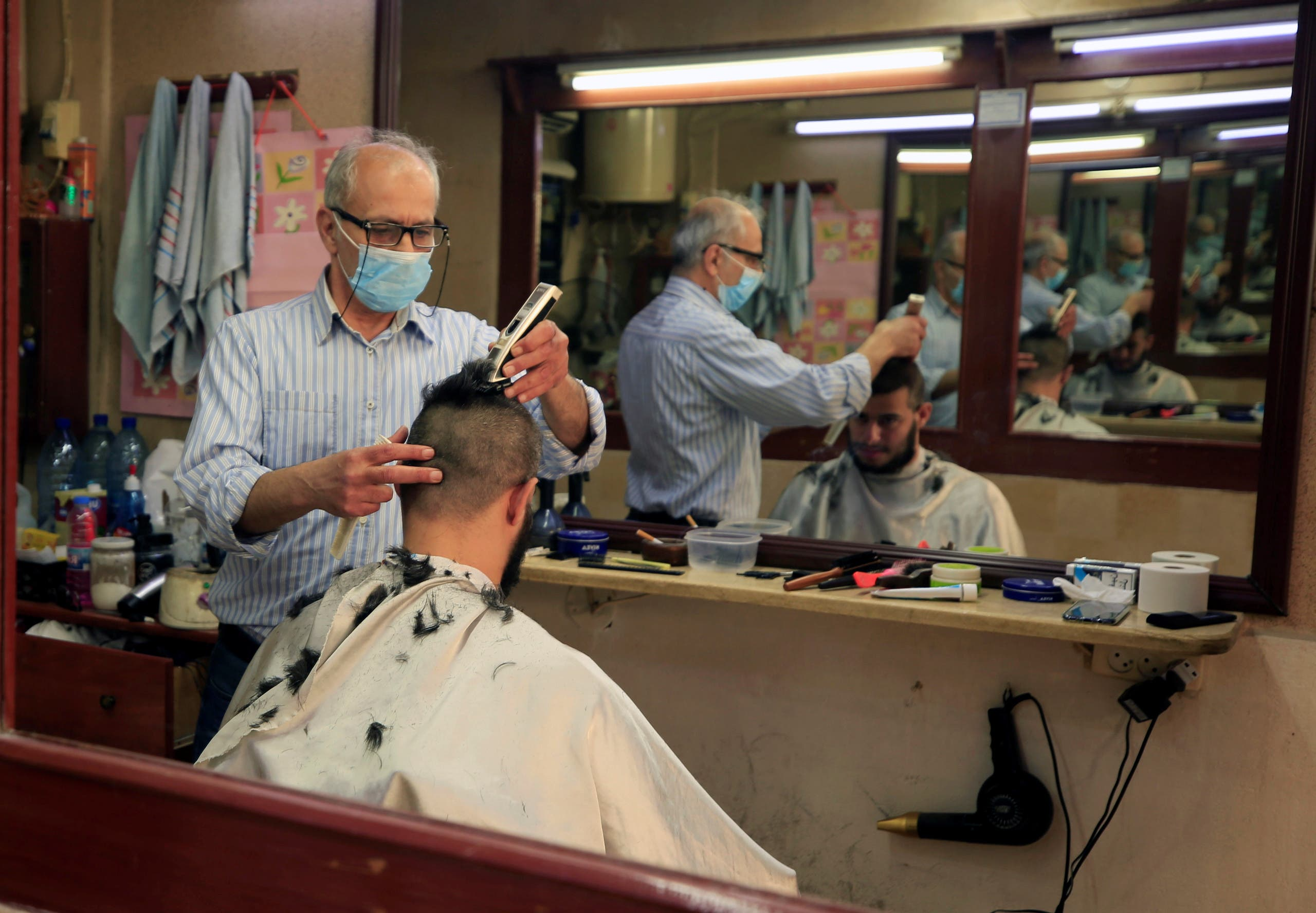 A barber wearing a protective mask shaves a customer's head at his shop, during a countrywide lockdown to combat the spread of the coronavirus disease (COVID-19) in Sidon, Lebanon April 23, 2020. REUTERS/Ali Hashisho