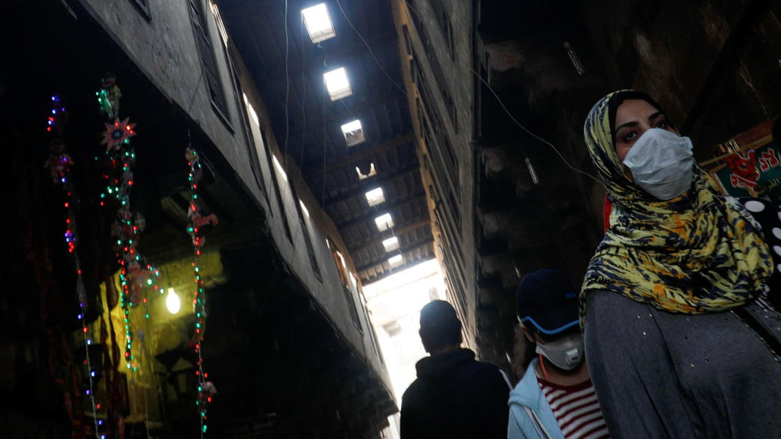 People wearing protective face masks, walk near traditional Ramadan products which are displayed for sale, amid concerns over the spread of the coronavirus disease (COVID-19) at Al Khayamia street in old Cairo, Egypt April 16, 2020. Picture taken April 16, 2020. REUTERS/Amr Abdallah Dalsh