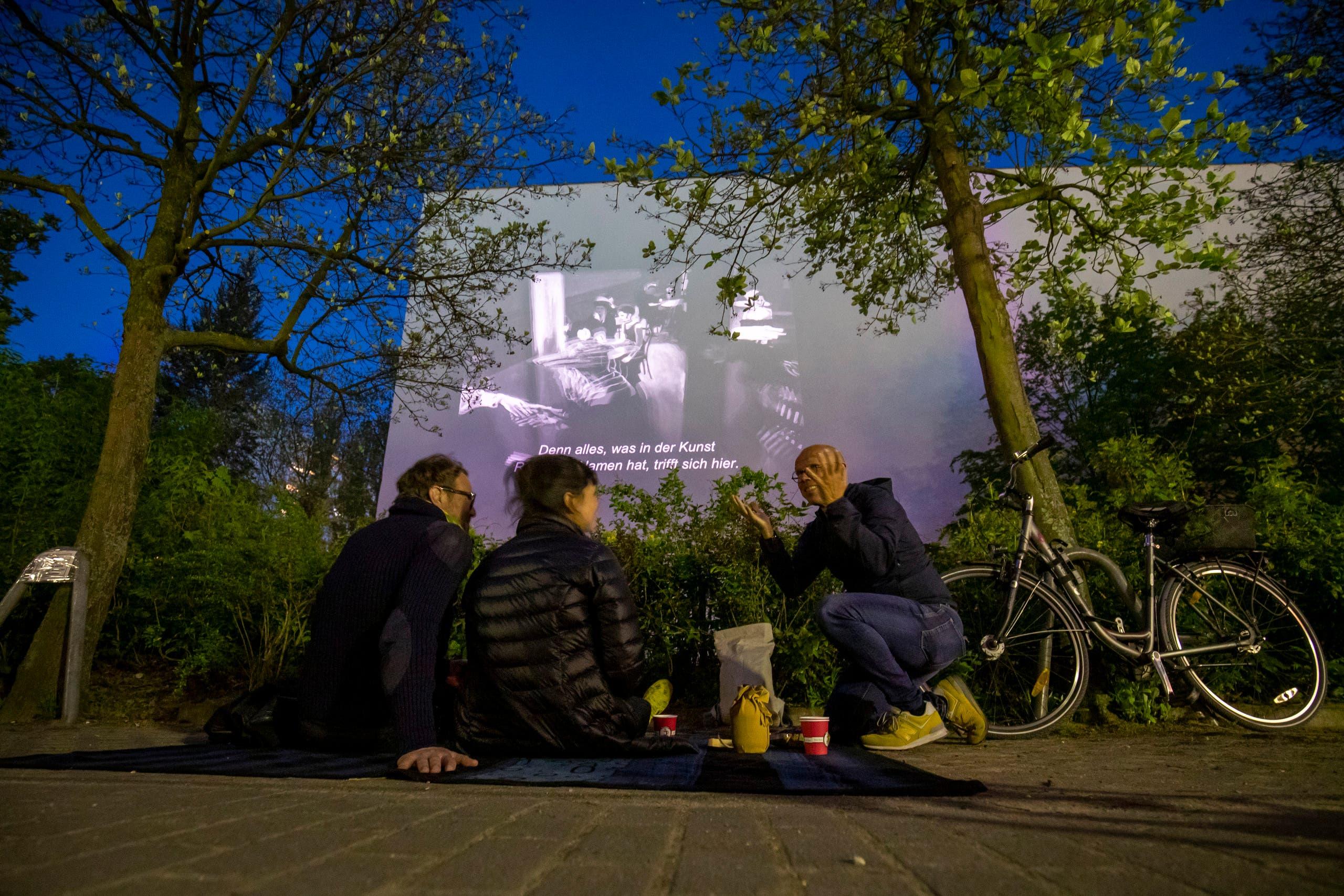 سكان جلسوا في الباحخة لمشاهدة الفيلم