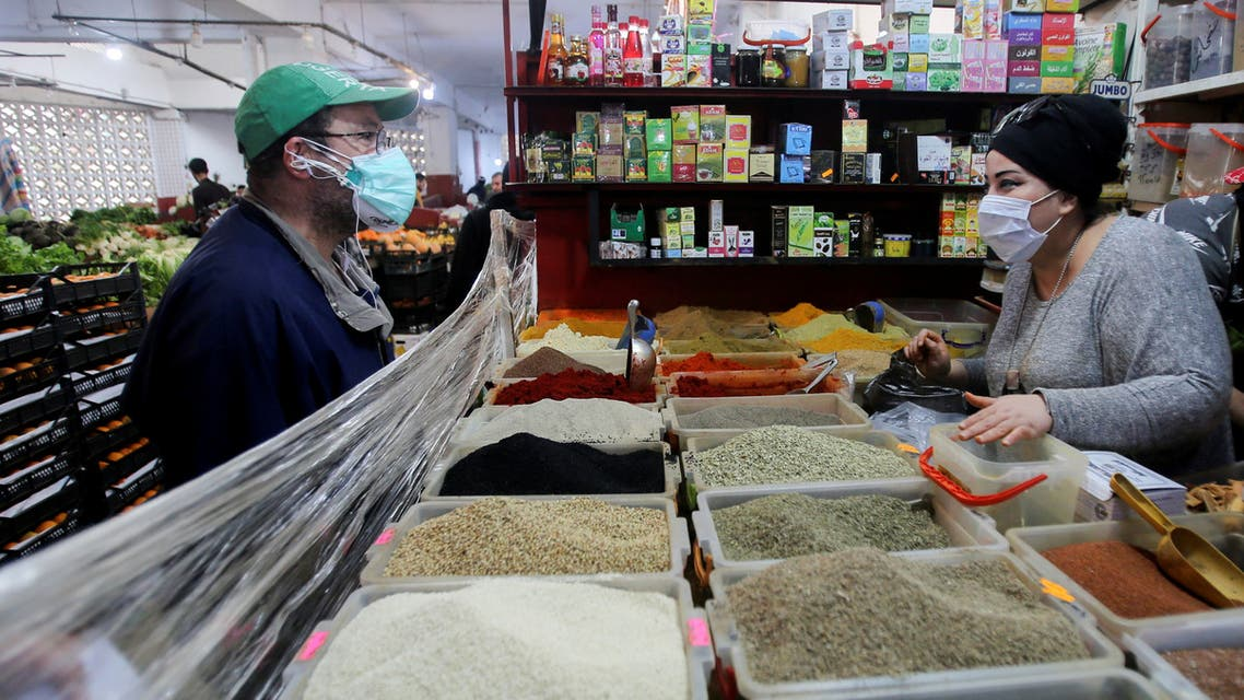 A vendor wearing a protective face mask serves a customer inside her shop, ahead of the Muslim holy month of Ramadan, amid concerns over the coronavirus disease (COVID-19), in Algiers, Algeria April 19, 2020. Picture taken April 19, 2020. REUTERS/Ramzi Boudina
