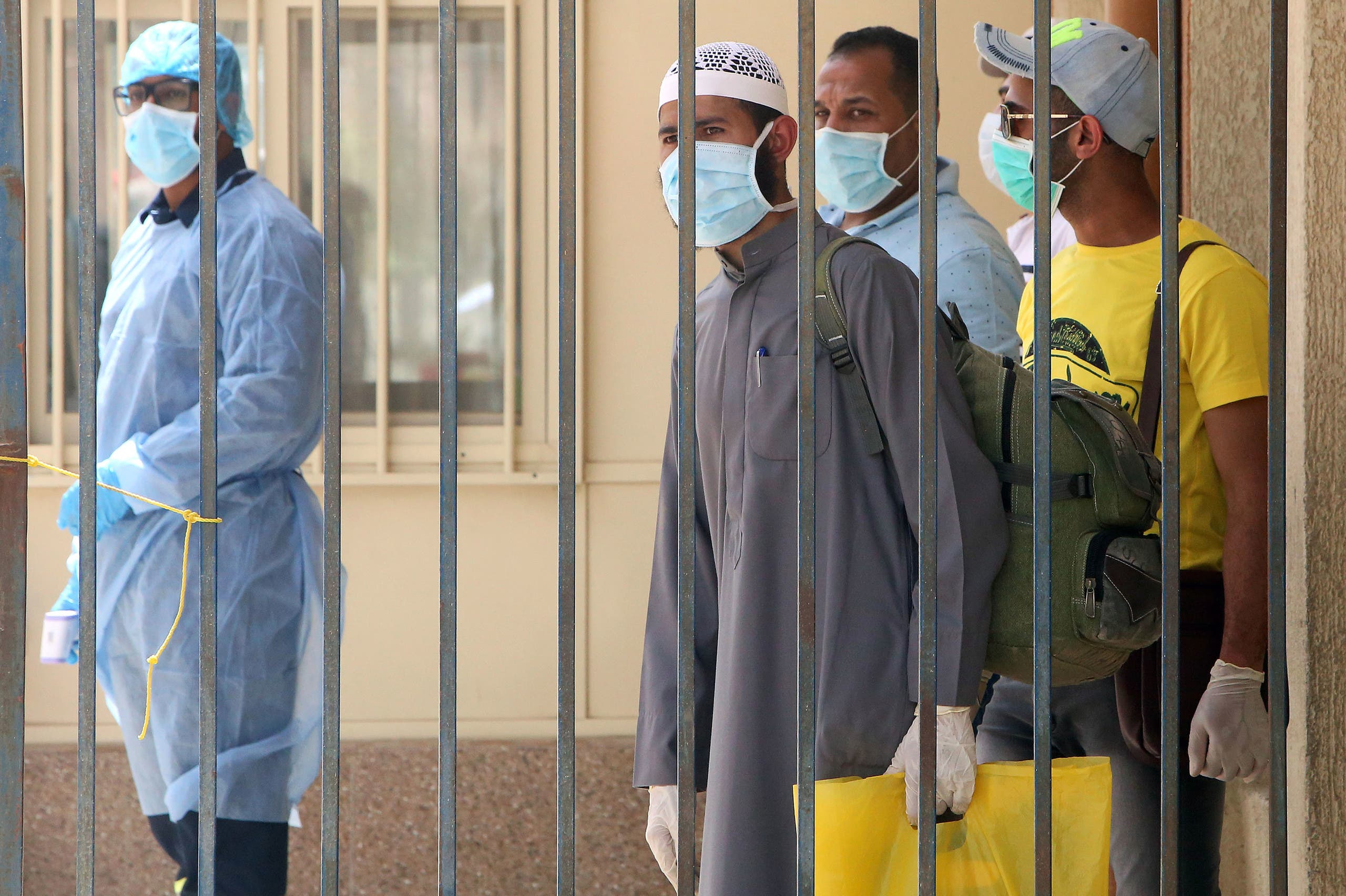 وافدون يرتدون كمامات في مركز قصدوه لتعديل أوضاعهم في الكويت ضمن مبادرة أطلقتها السلطات في ظل تفشي كورونا