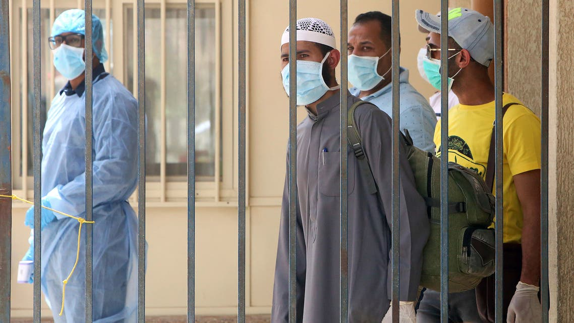 Egyptians are pictured inside a school that was turned into a centre to receive residency violators wishing to avail an amnesty Kuwait announced for April, amid the coronavirus COVID-19 pandemic crisis, in Kuwait City on April 6, 2020.