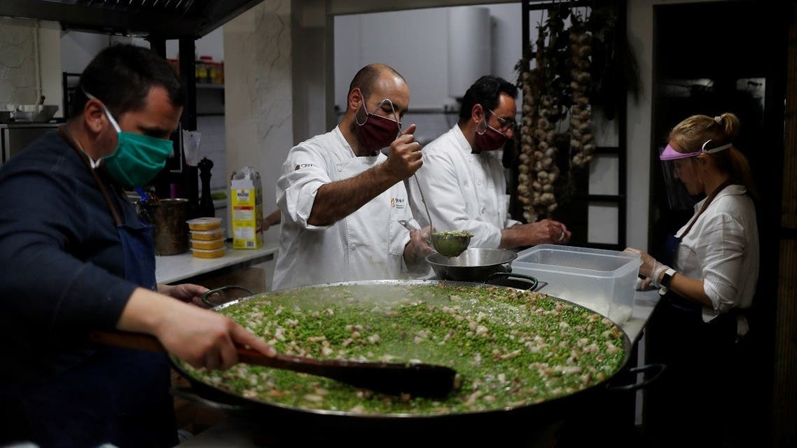 Benito Gomez (2nd L), chef of two-Michelin-starred restaurant Bardal, cooks food with other chefs and volunteers during a food distribution campaign for families following the outbreak of the coronavirus disease (COVID-19), at a social lunchroom in Ronda, southern Spain. (Reuters)