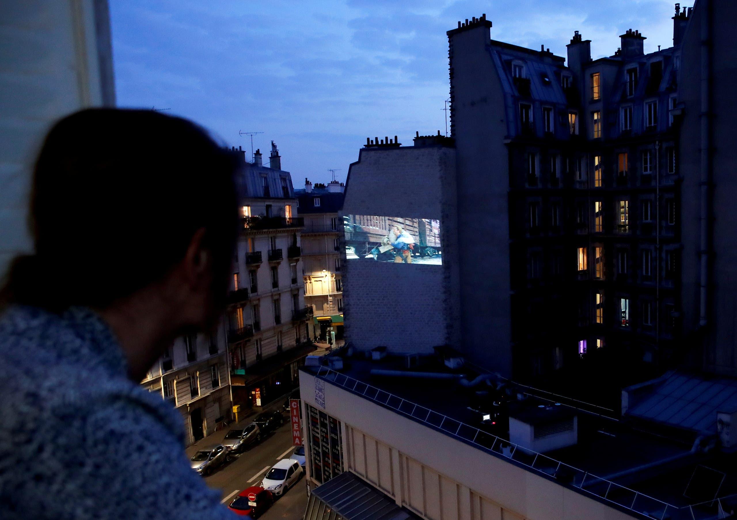 أحد السكان يشاهد الفيلم من شرفته