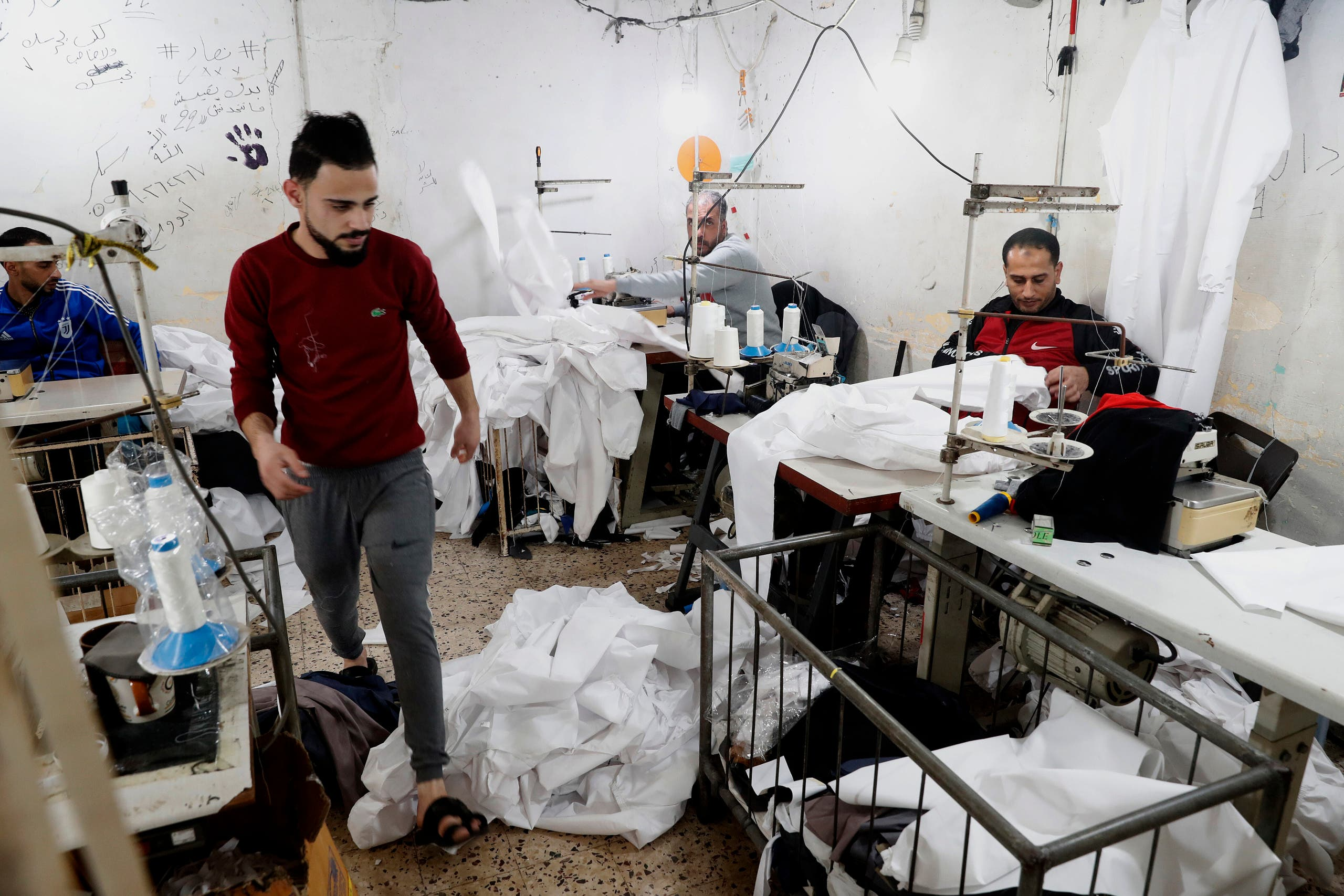 Palestinians make protective overalls to help shield people from the coronavirus, that will be exported to Israel, at a local factory, in Gaza City, Monday, March 30, 2020. (AP)