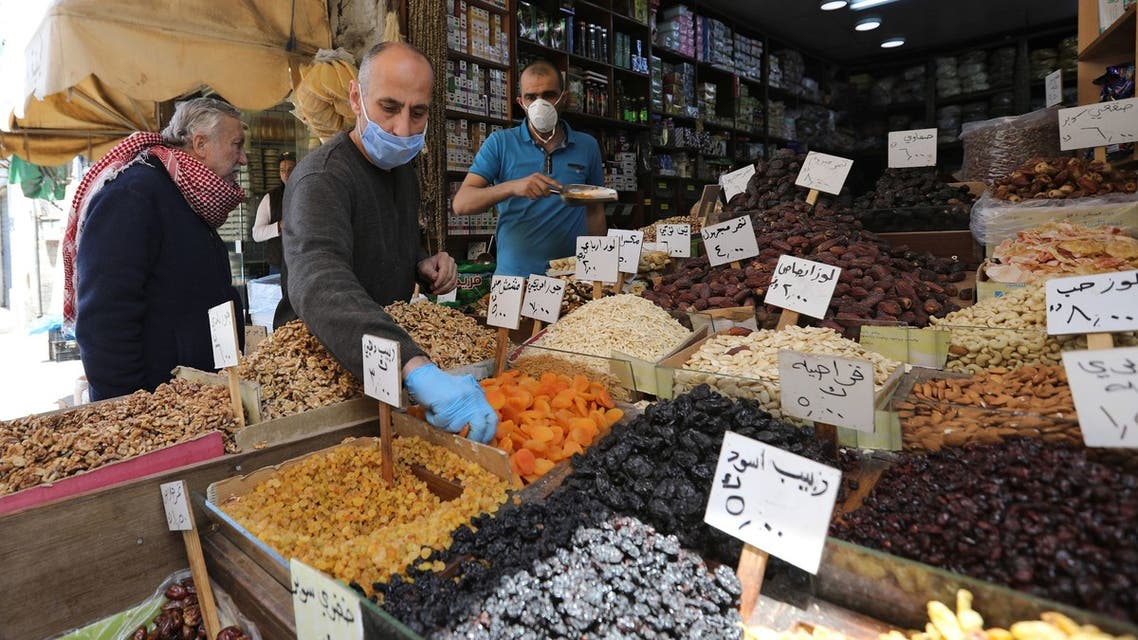 Vendors wearing protective face masks serve customers at a shop, ahead of the Muslim holy month of Ramadan, amid concerns over the coronavirus disease (COVID-19), in Amman, Jordan April 21, 2020. Picture taken April 21, 2020. REUTERS/Muhammad Hamed