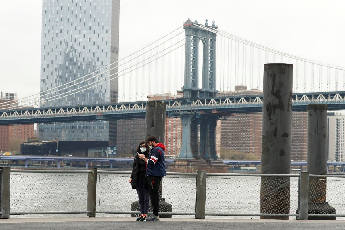 Pedestrians wearing masks walk in Brooklyn Bridge Park as the spread of the coronavirus disease (COVID-19) outbreak continues in the Brooklyn borough of New York City. (Reuters)