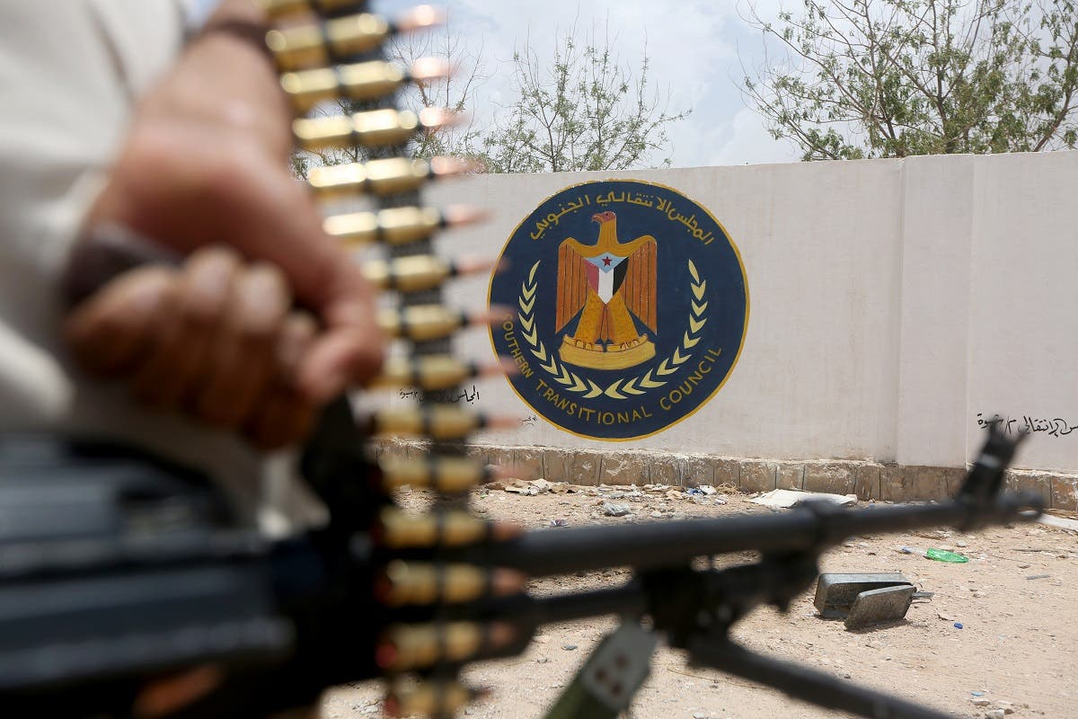 A Yemeni government soldier holds a weapon as he stands by an emblem of the STC at the headquarters of the separatist Southern Transitional Council in Ataq, Yemen August 27, 2019. (Reuters)