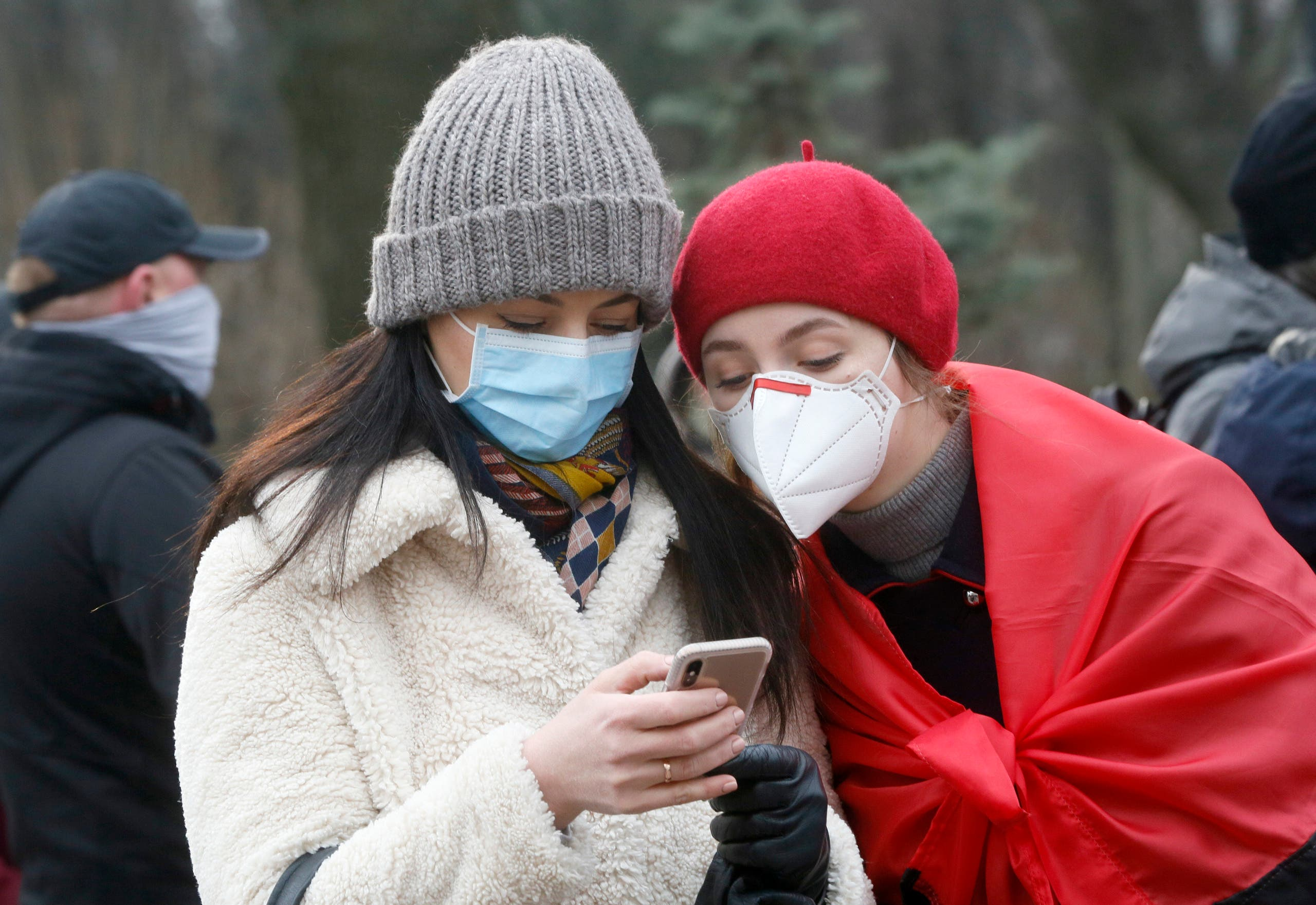 Two women wearing face masks look at the latest news on a phone. (File photo: AP)