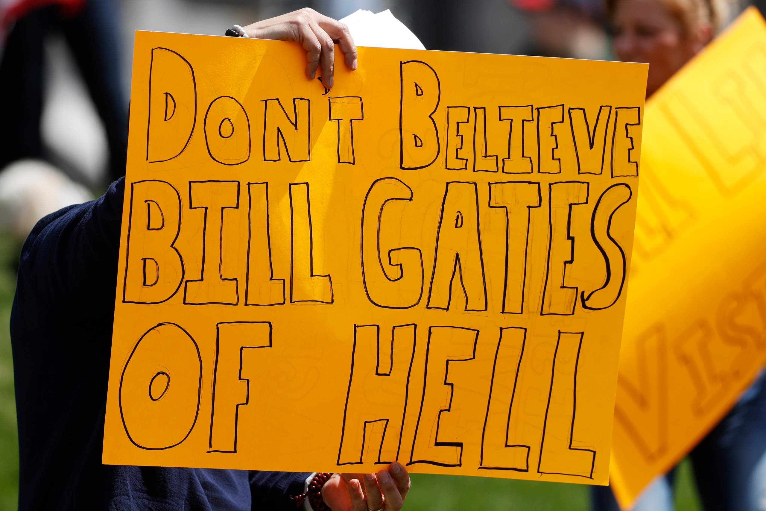 A protester waves a placard against American business magnate and philanthropist Bill Gates during a protest against the stay-at-home order issued by Colorado Governor Jared Polis to stem the spread of the new coronavirus, on April 19, 2020, in Denver. (AP)