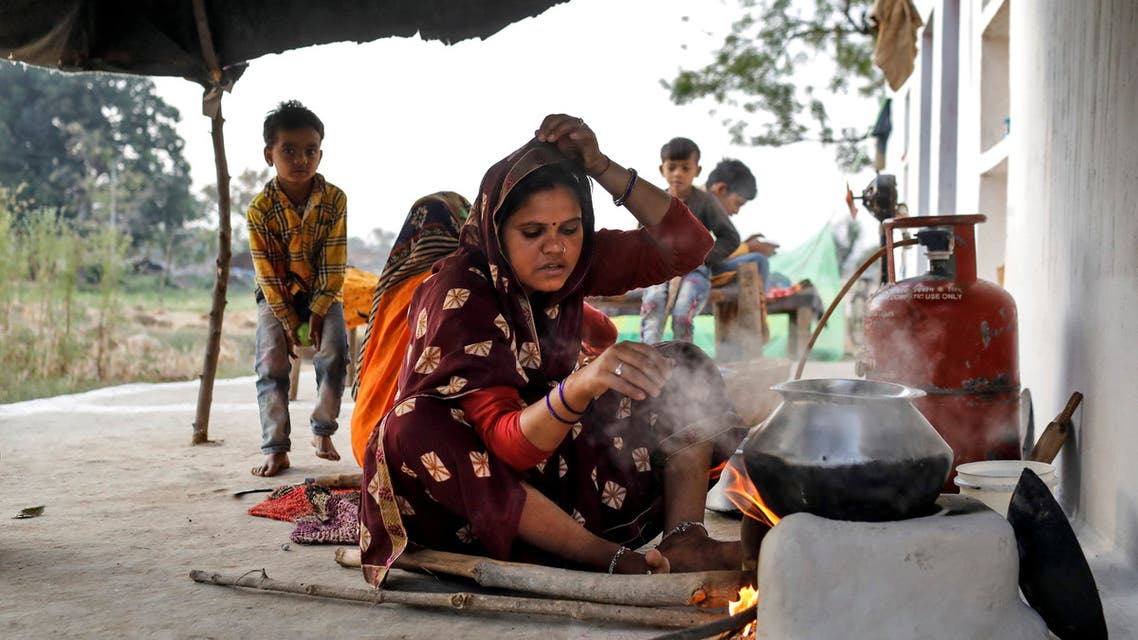 A migrant worker cooks food for her family after she returned home from New Delhi during nationwide lockdown in India due to the coronavirus pandemic, on April 8, 2020. (Reuters)