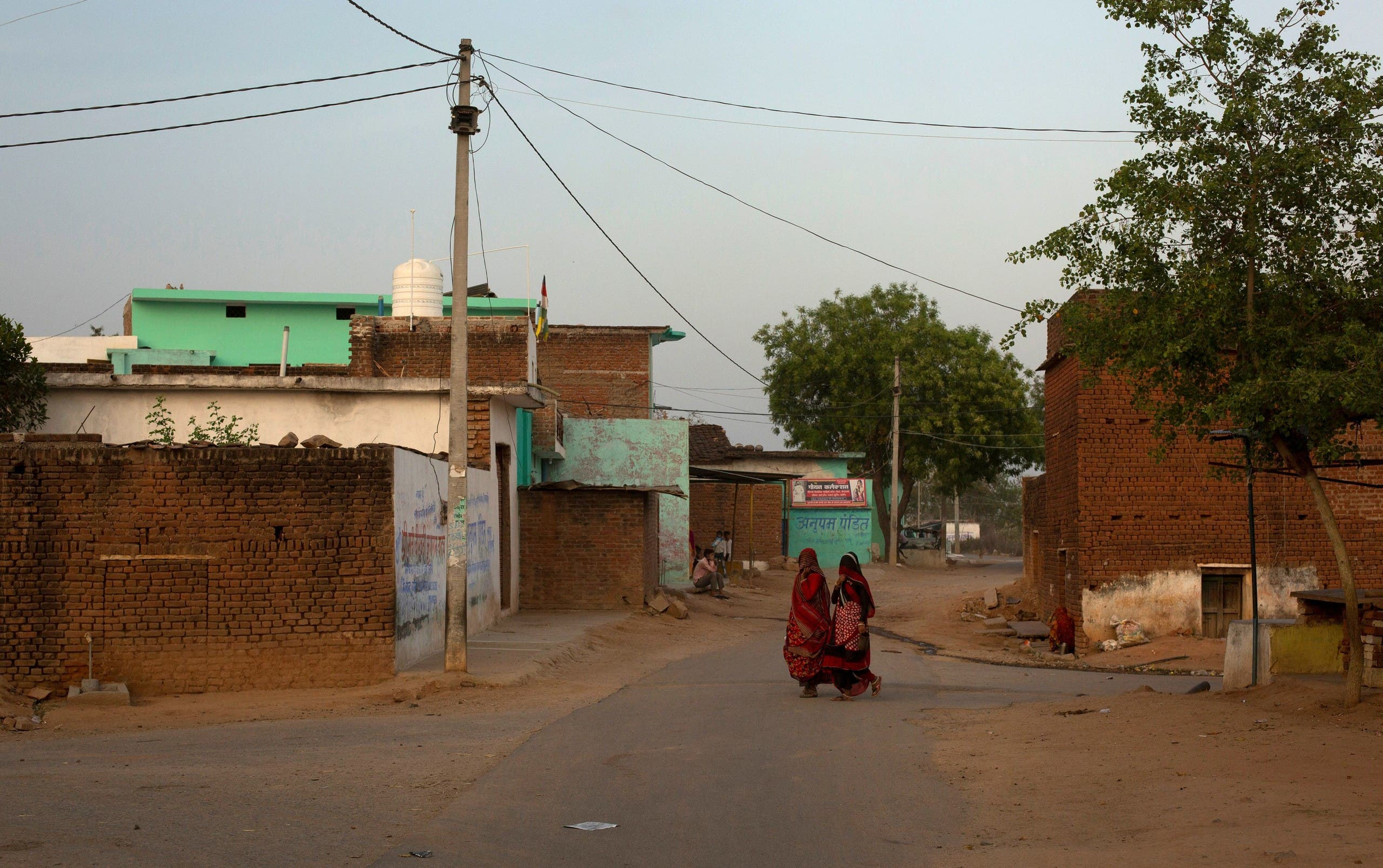 Women walk through an empty street during nationwide lockdown, in Jugyai village in the central state of Madhya Pradesh, India, on April 8, 2020. (Reuters)