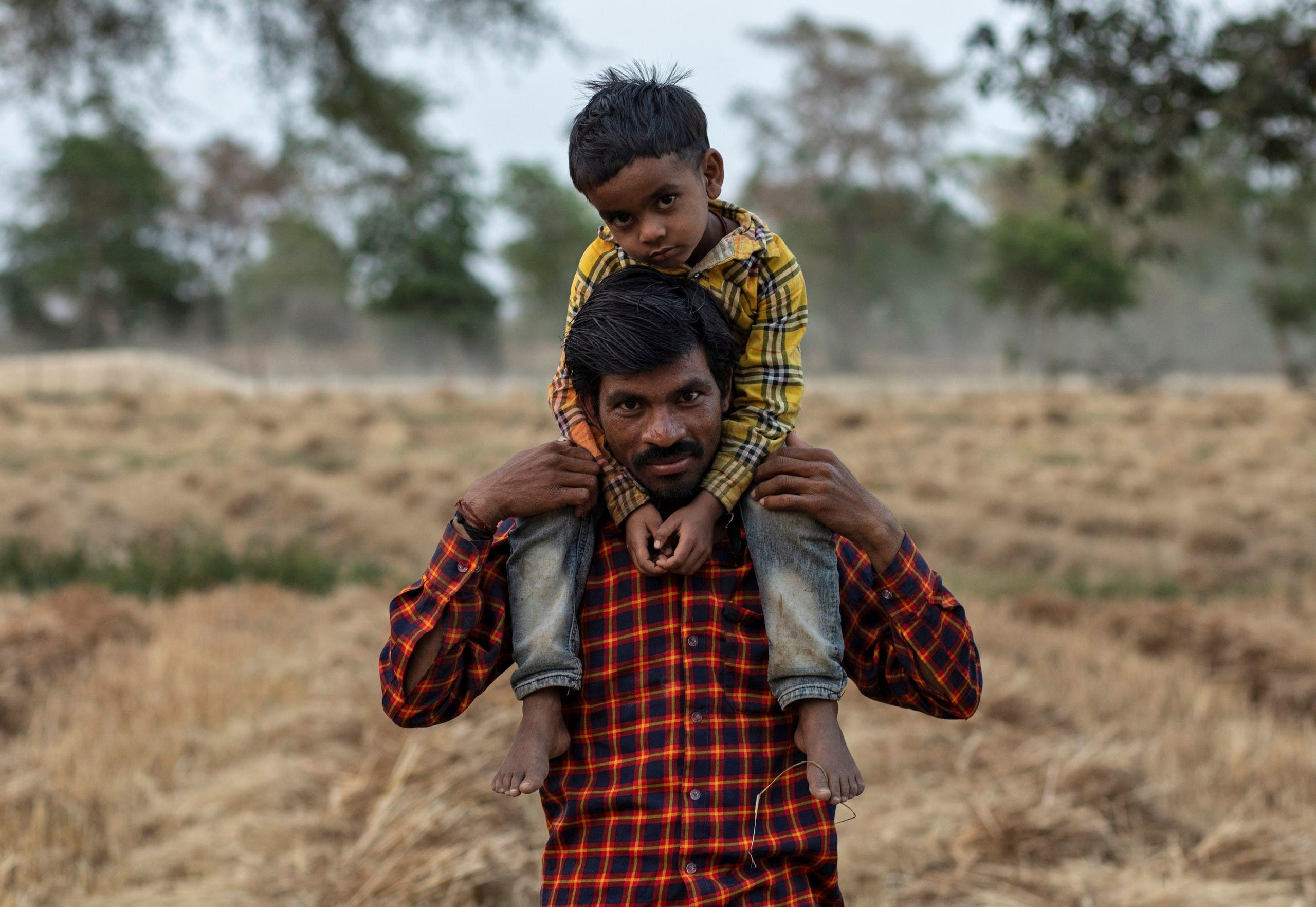 Dayaram Kushwaha poses for a portrait with his 5-year-old son, Shivam, after he returned to his home from New Delhi during nationwide lockdown in India due to coronavirus pandemic. (Reuters)