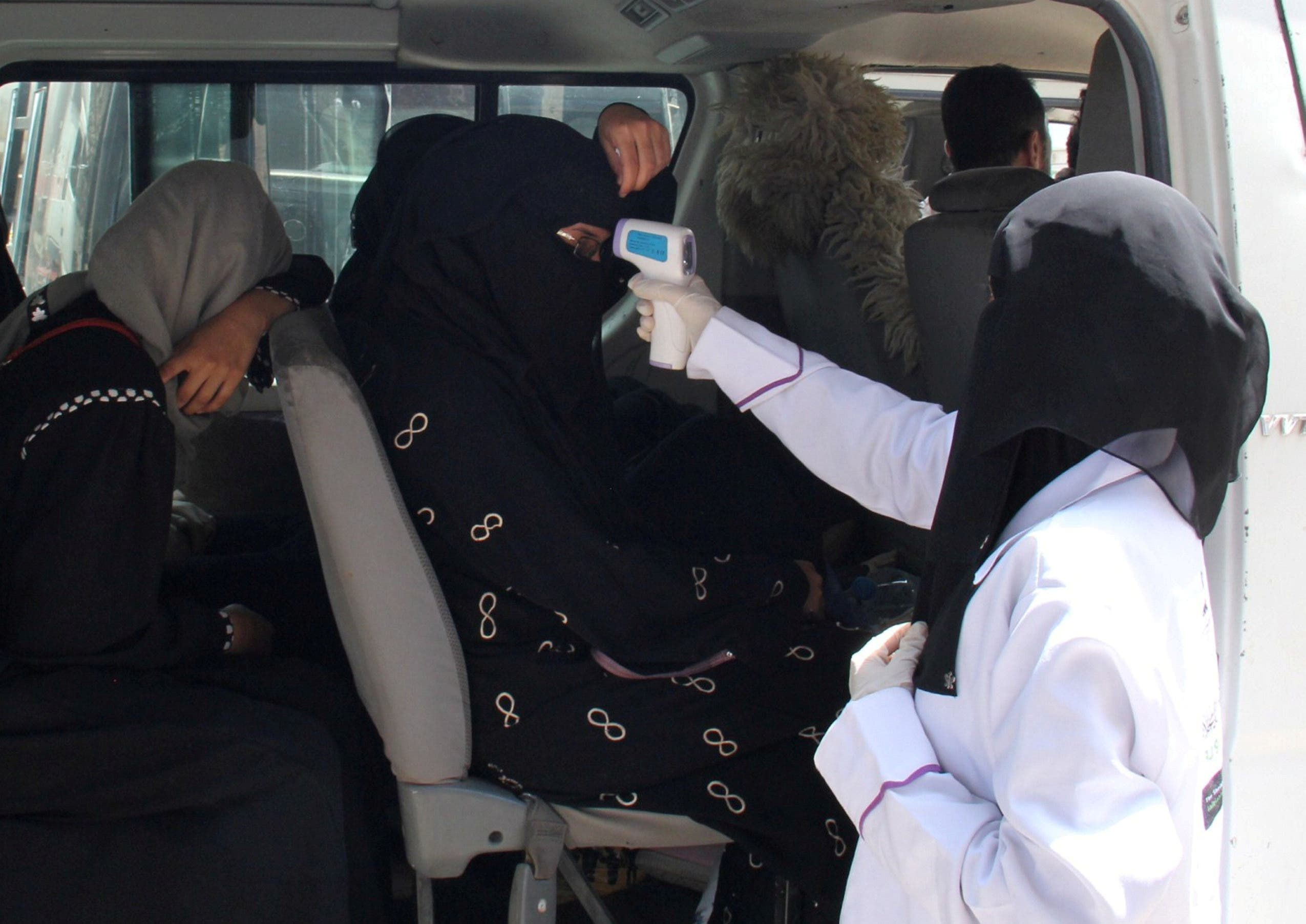 A health worker takes temperature of passengers of a van, amid fear of coronavirus disease, on the outskirts of Taiz, Yemen on April 12, 2020. (Reuters)