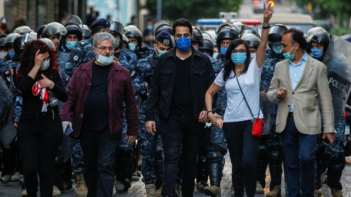 Lebanese demonstrators wear face masks during a protest against the collapsing Lebanese pound currency outside Lebanon's Central Bank in Beirut, Lebanon April 23, 2020. (Reuters)