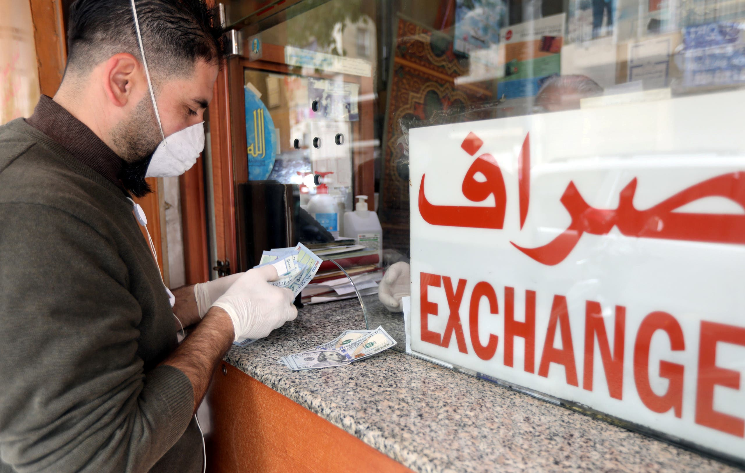 A customer wearing a face mask and gloves, is served at a counter of a currency exchange store, during a countrywide lockdown to combat the spread of coronavirus disease (COVID-19) in Beirut, Lebanon. (Reuters)