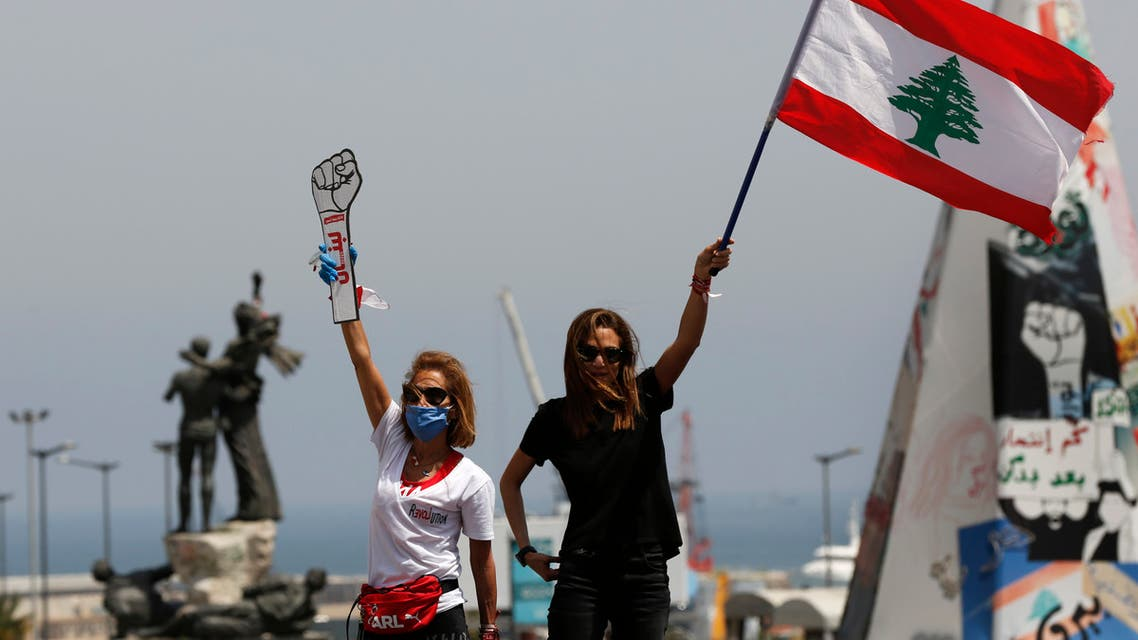 Anti-government protesters stand on the top of their cars and wave a Lebanese flag and a cardboard fist labelled Revolution in Beirut on April 22, 2020. (AP)