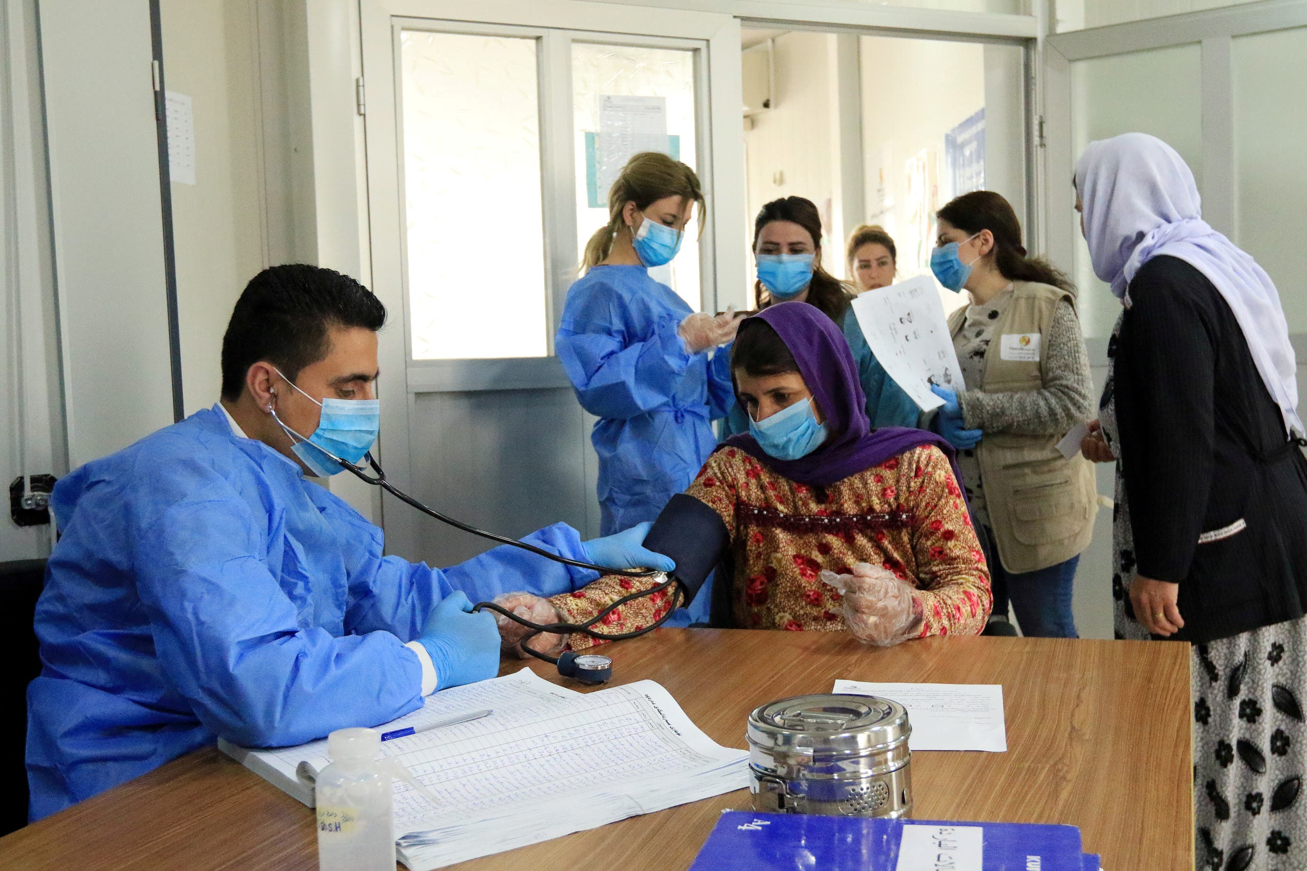 A doctor checks the blood pressure of a Yazidi displaced woman, as they wear protective face masks, following the coronavirus outbreak, at medical Center in the Sharya camp in Duhok, Iraq March 7, 2020. (Reuters)