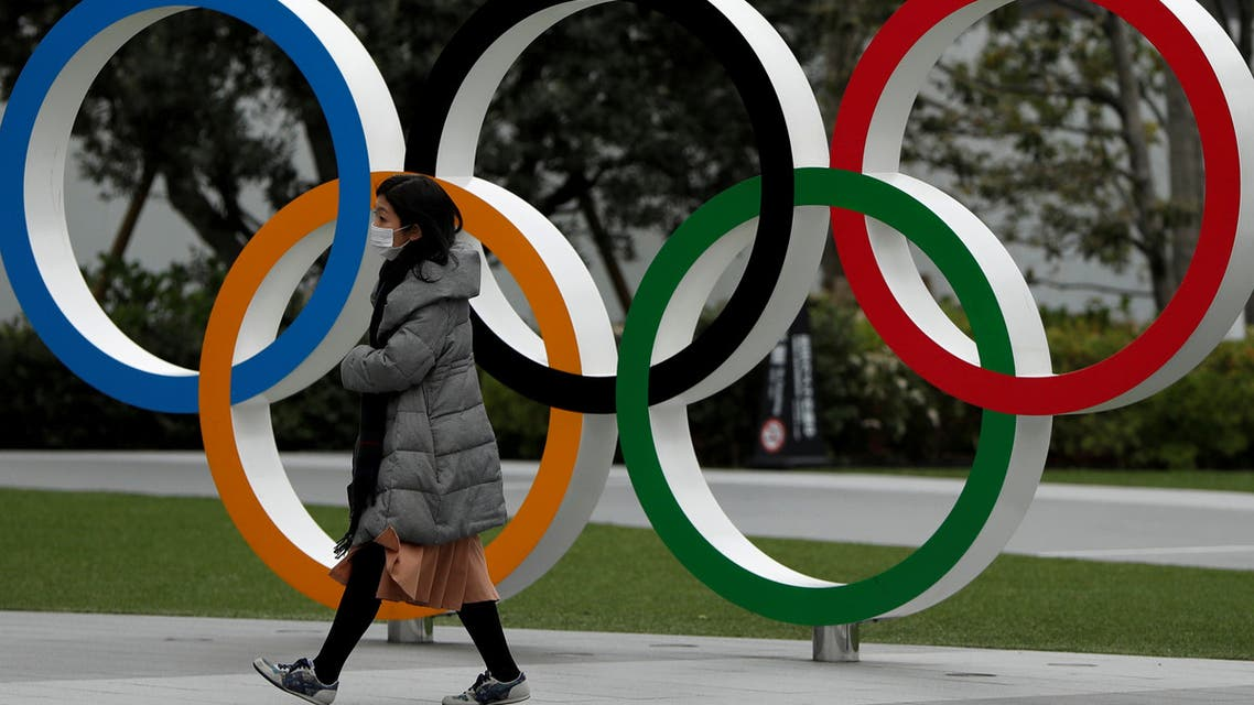 FILE PHOTO: A woman wearing a protective face mask, following an outbreak of the coronavirus disease (COVID-19), walks past the Olympic rings in front of the Japan Olympics Museum, in Tokyo, Japan March 30, 2020. REUTERS/Issei Kato/File Photo