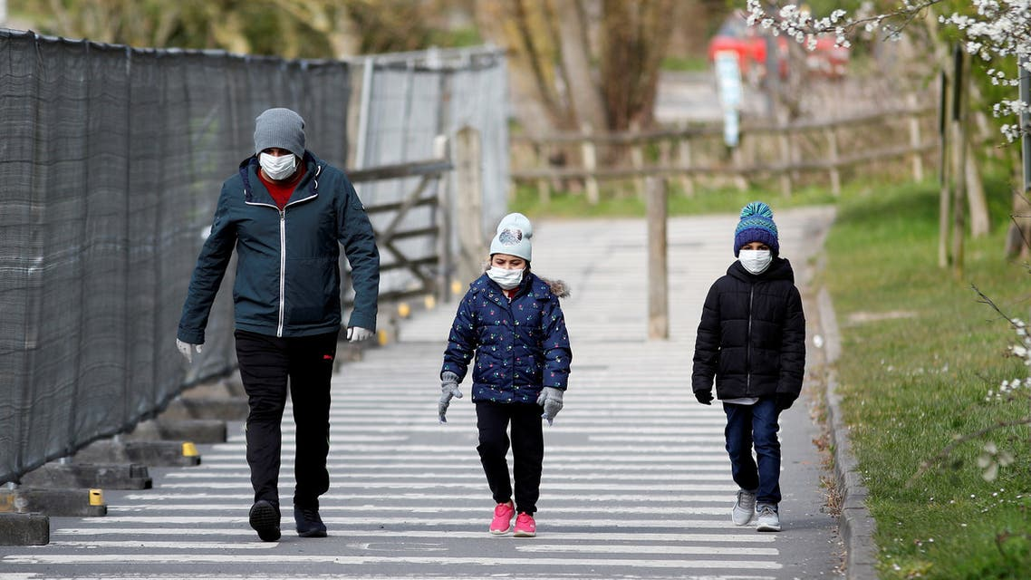 A man and children wearing protective face masks walk near a Chessington World of Adventures car park, which has been turned into a testing facility as the spread of the coronavirus disease (COVID-19) continues, Chessington, Britain. (Reuters)