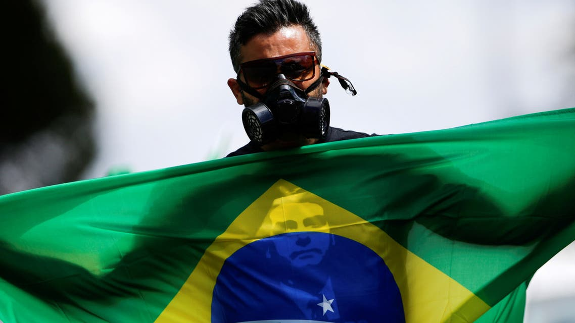 A pro-Bolsonaro protester with a Brazil flag and a gas mask, Brasilia, April 27. (Reuters)