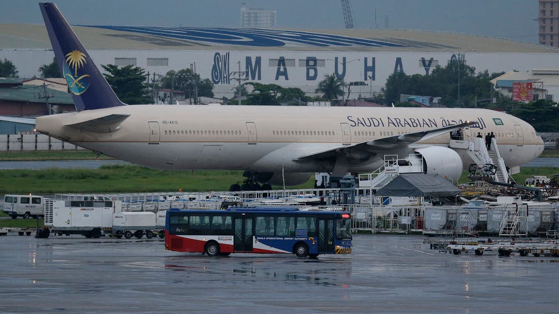 A passenger bus passes by the Saudi Arabian Airlines plane Flight SV872 from Jiddah as it stays at an isolated area at Manila's International Airport in Pasay. (AP)