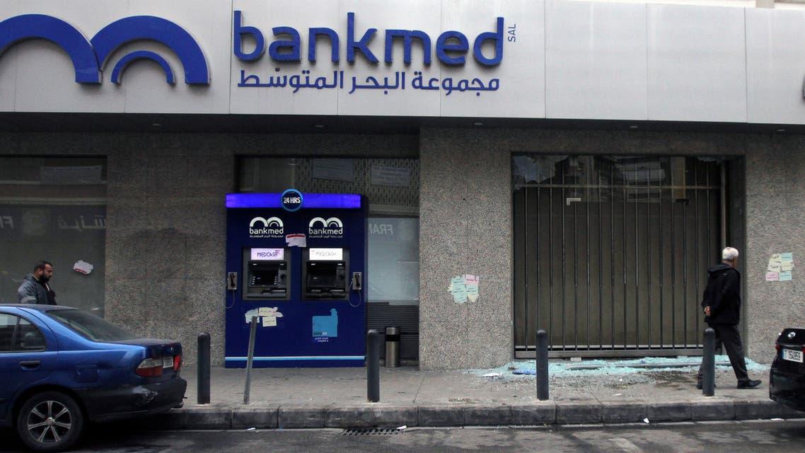 Men walk near broken glass from a damaged Bankmed branch in Tripoli, Lebanon November 27, 2019. (Reuters)