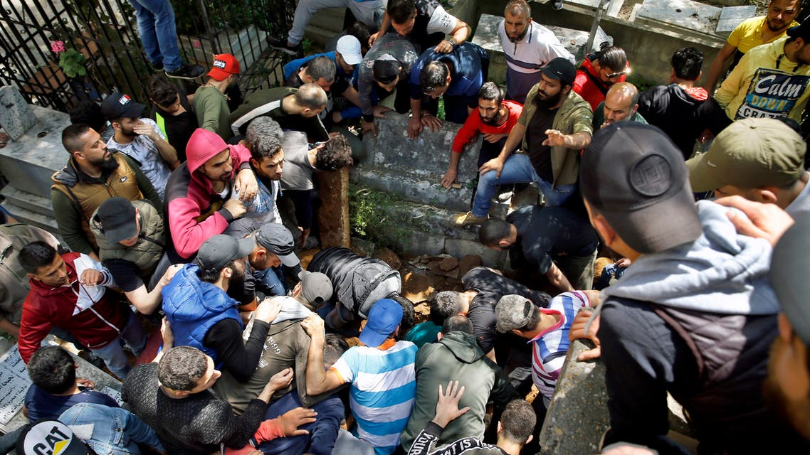 Mourners unload a coffin of Fawwaz Samman, who was shot by soldiers during confrontations that began Monday night and died in a hospital hours later, into a grave, in the northern city of Tripoli, Lebanon, Tuesday, April 28, 2020. Hundreds of protesters set fire to two banks and hurled stones at soldiers, who responded with tear gas and batons in renewed clashes triggered by an economic crisis spiraling out of control amid a weeks-long virus lockdown. (AP Photo/Bilal Hussein)