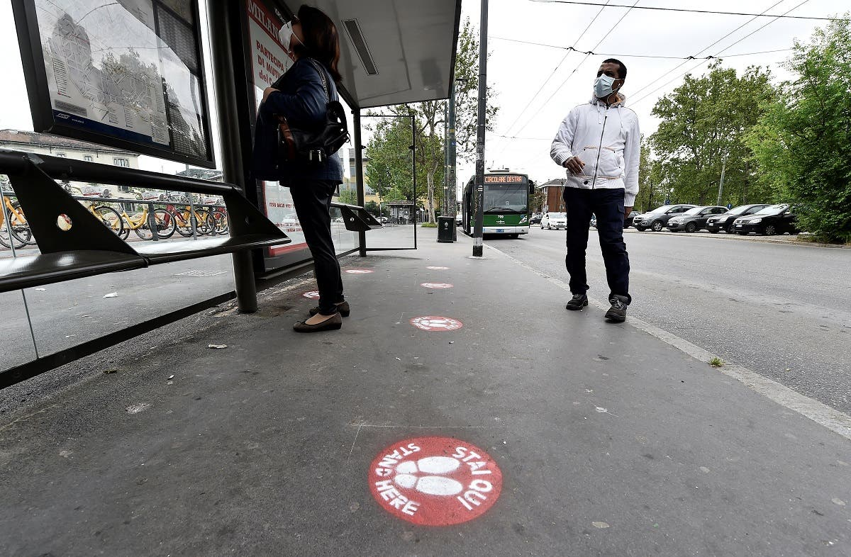 People wearing protective face masks wait for a bus at the stop with social distancing signs on the pavement as the spread of the coronavirus continues, in Milan, Italy, on April 27, 2020. (Reuters)