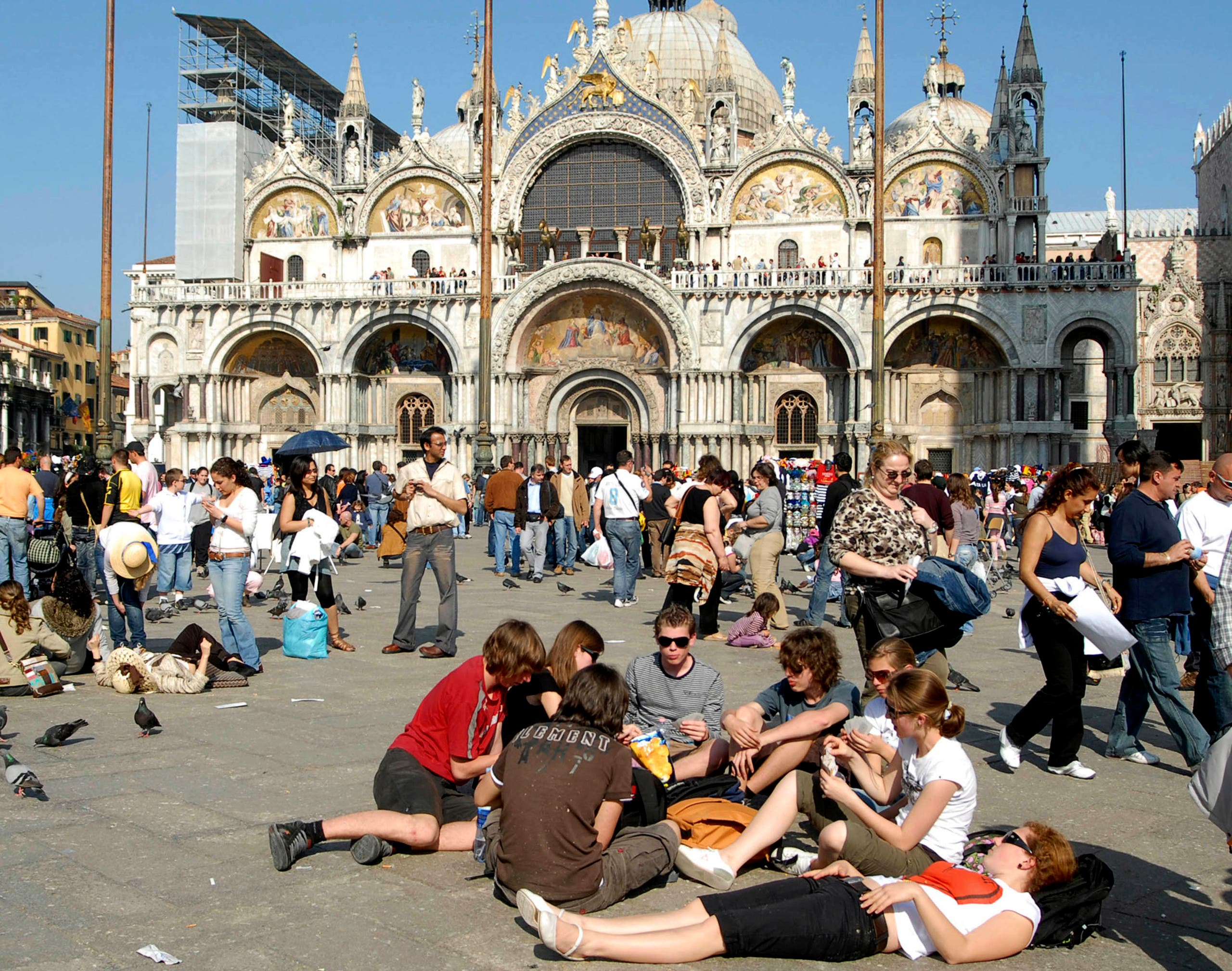 Tourists enjoy the sun in a crowded St.Mark's Square, in Venice, northern Italy, with St. Mark's Basilica in the background, in this May 1, 2007 photo. (AP)