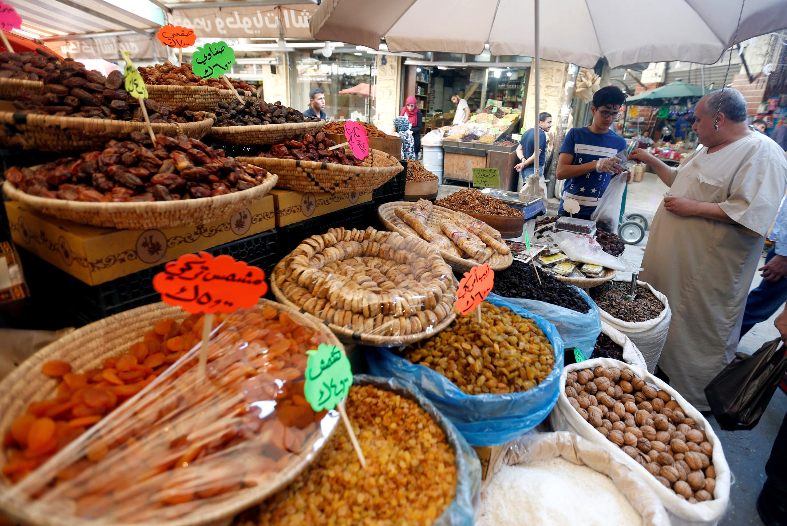 Muslim people buy dates for Iftar during the holy month of Ramadan at a market area in Amman. (File photo: Reuters)