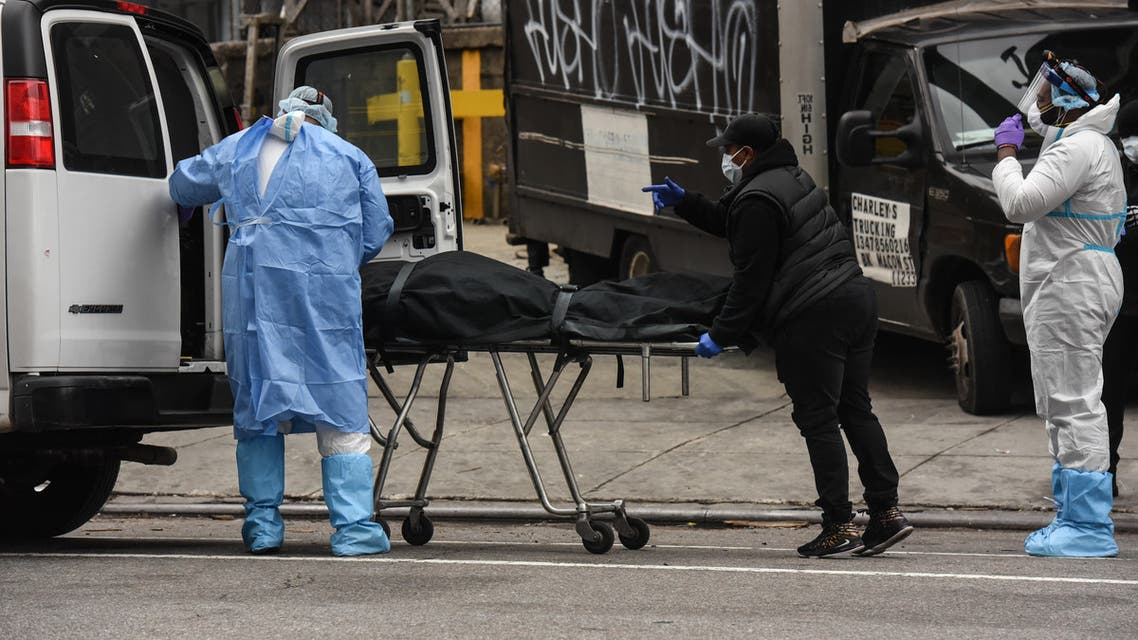NEW YORK, NY - APRIL 27 : A funeral worker is assisted moving a deceased patient into a van at the Brooklyn Hospital Center on April 27, 2020 in the Brooklyn borough of New York City. The Brooklyn Hospital Center has been part of the pandemic's epicenter in New York City. Stephanie Keith/Getty Images/AFP