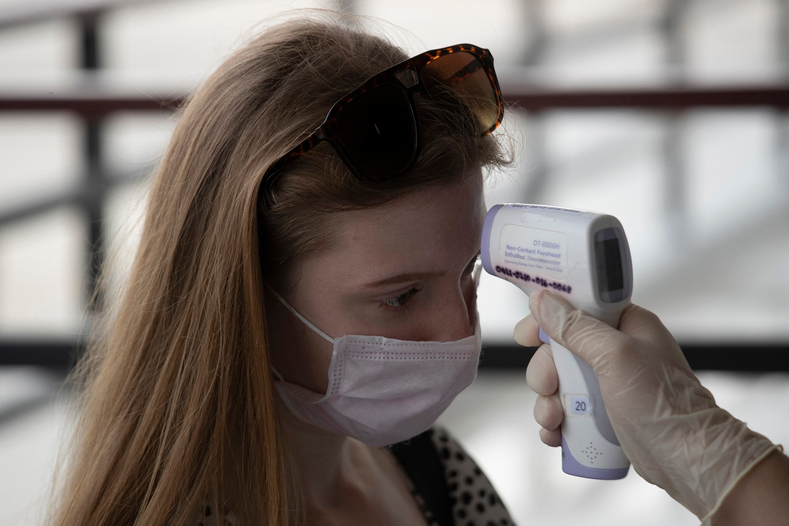 A health officer checks the temperature of a tourist who wants to extend visa at Immigration Bureau in Bangkok on March 27, 2020. (AP)