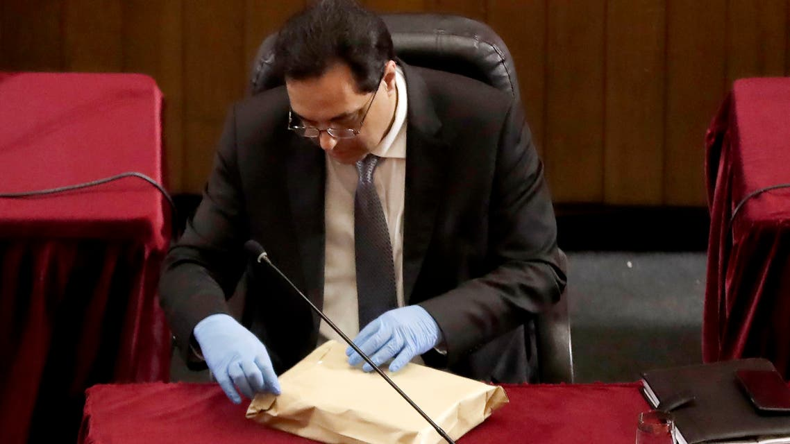 Lebanese Prime Minister Hassan Diab wearing gloves opens an envelope during a parliament meeting at the Unesco Palace in the capital Beirut, on April 21, 2020. Lebanon's parliament met in a conference hall to allow for social distancing between lawmakers amid the coronavirus pandemic, while outside anti-government protesters demonstrated in a car convoy. As the country struggles with a battered economy, MPs approved a $120 million loan from the World Bank to help fight COVID-19, which has officially infected 677 people and killed 21 nationwide.
