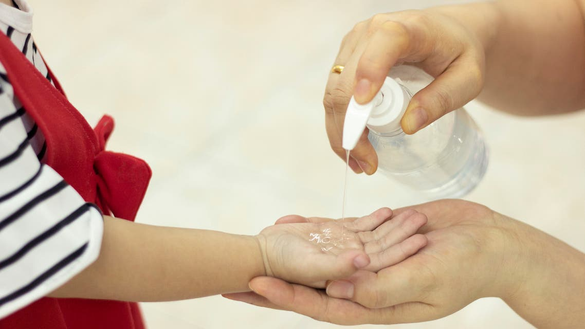 Kid using sanitizer alcohol gel clean hand protection infection virus bacteria cleanser stock photo