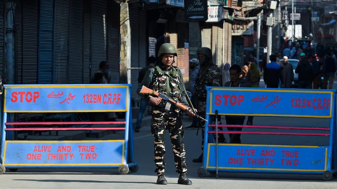 A soldier stands guard at a roadblock following restrictions imposed as a preventive measure against the COVID-19 coronavirus in Srinagar on March 19, 2020.