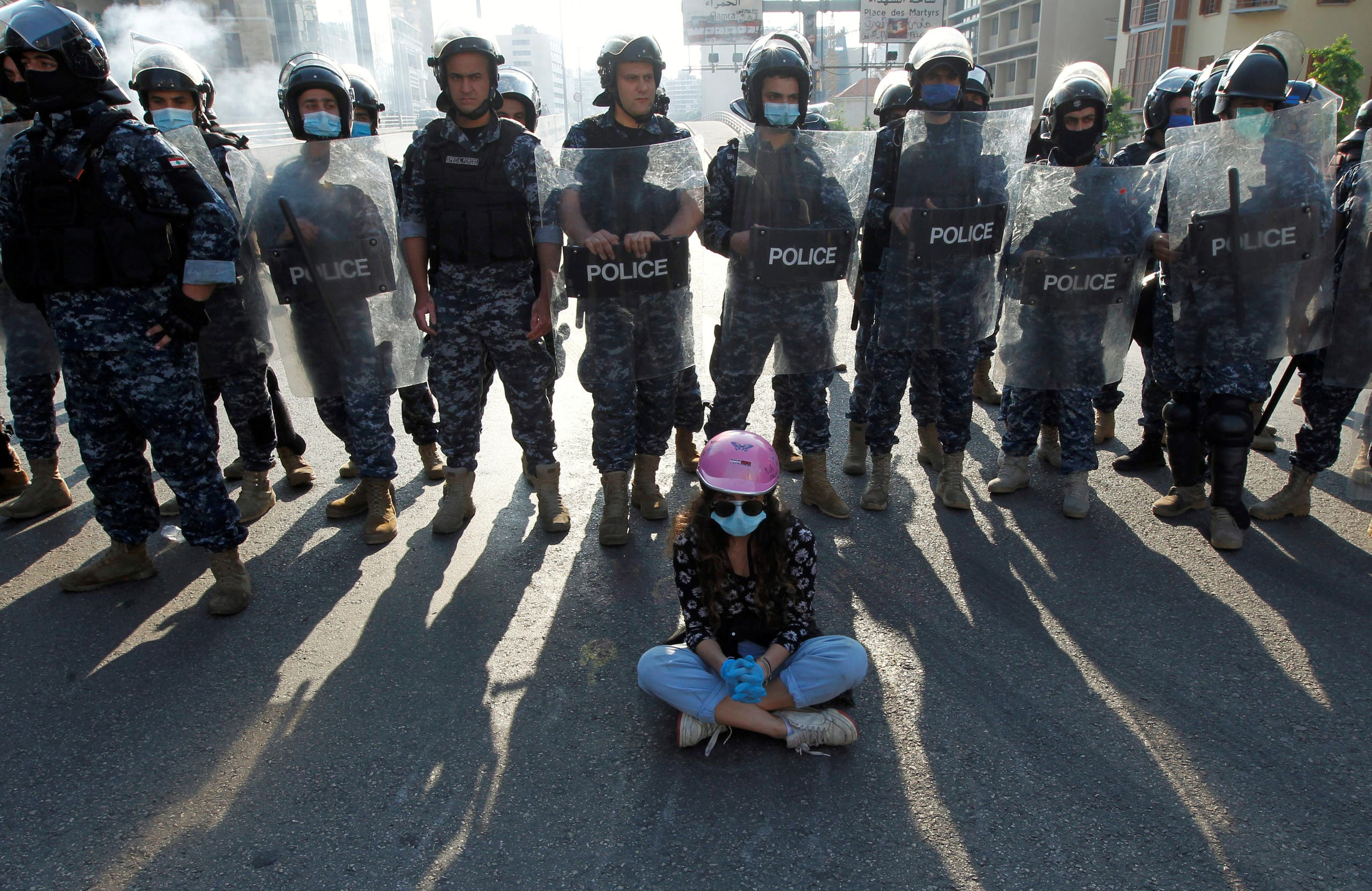 A demonstrator sits on the ground in front of Lebanese police officers during a protest against growing economic hardship in Beirut, Lebanon April 28, 2020. (Reuters)