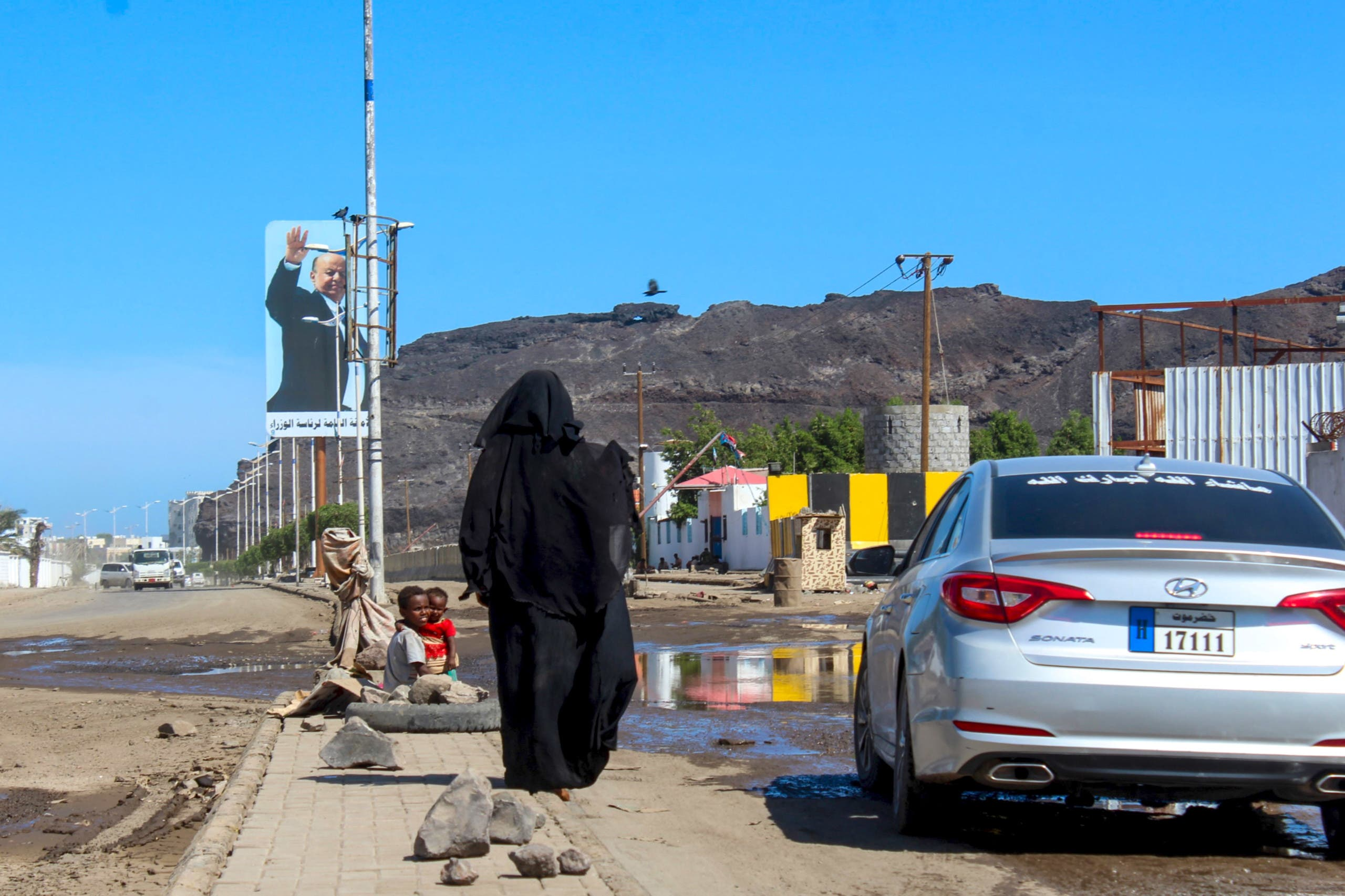 A woman begs for money, next to her children, from a vehicle in the southern Yemeni city of Aden on April 27, 2020, during the Muslim holy month of Ramadan. (File photo)