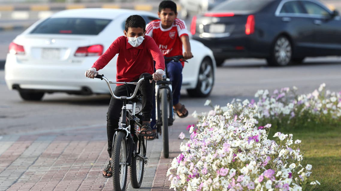 A boy wears a protective face mask, as he rides a bicycle, after Saudi Arabia imposed a temporary lockdown on the province of Qatif, following the spread of coronavirus, in Qatif, Saudi Arabia March 10, 2020. REUTERS/Stringer