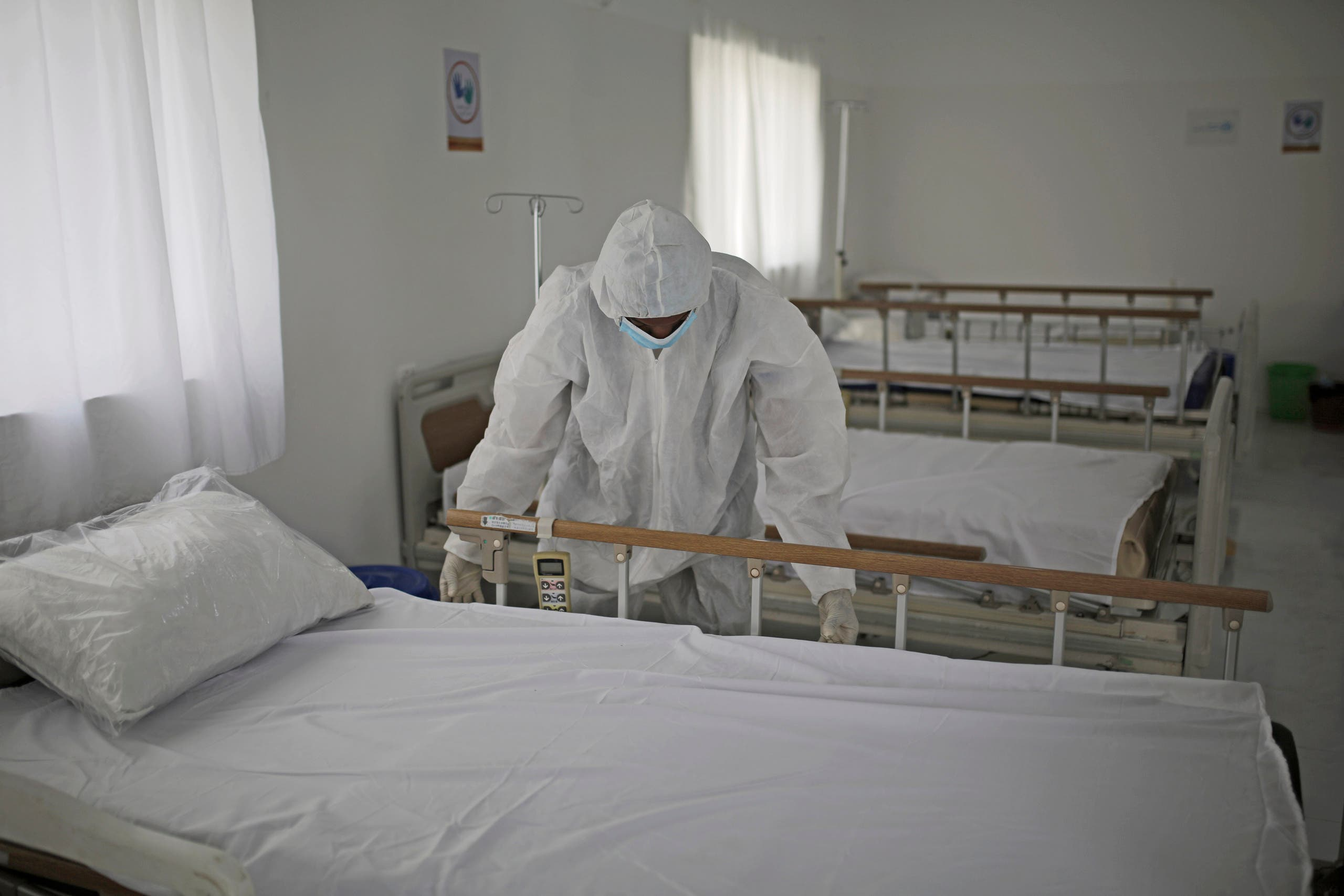 A medical staff member adjusts the sheets on a bed as personnel setup a coronavirus quarantine ward at a hospital in Sanaa, Yemen on March 15, 2020. (AP)