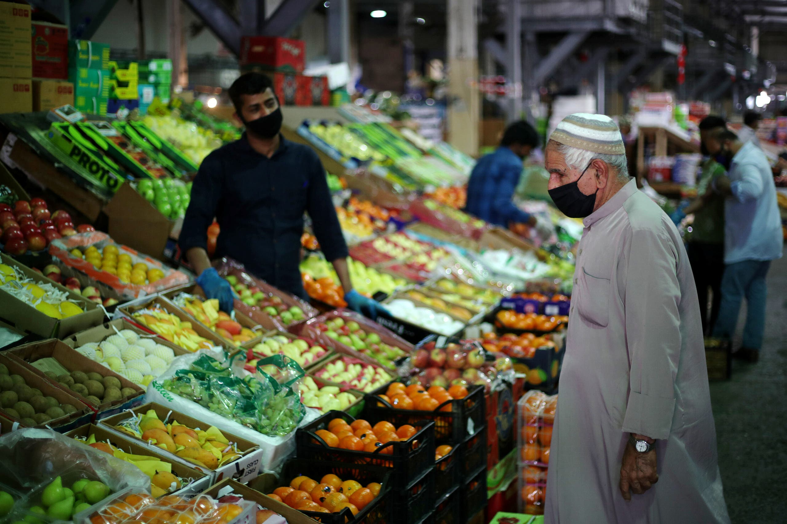 رجل يتبضع في سوق بالمنامة مرتدياً كمامة