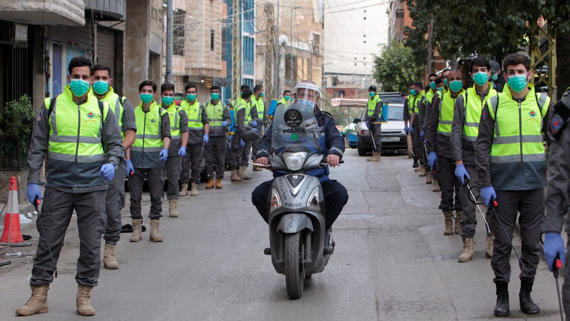 Volunteers from Hezbollah's Islamic health unit stand in preparation to sanitize streets as precaution against the spread of coronavirus disease (COVID-19), during a media tour organised by Hezbollah officials in Beirut's southern suburb. (Reuters)